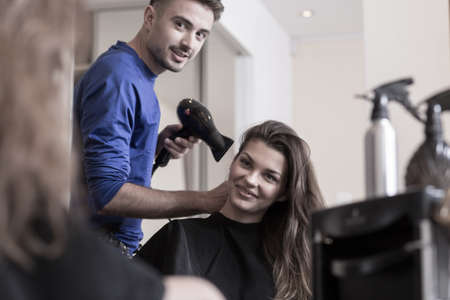 male hair: Beautiful smiling woman and her hairdresserwith a hairdryer