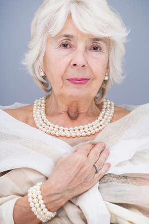 Elegant, senior woman with pearl necklace and bracelet, wearing white shawl
