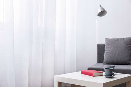 small table: Book and two cups lying on small table. Room with white curtain, lamp and grey sofa.
