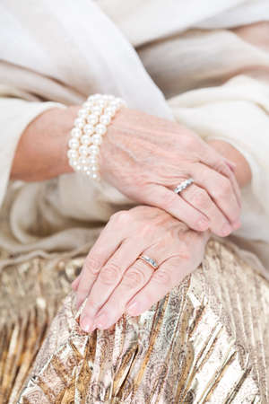 aristocrat: Close up of rich, senior womans hands. Woman with pearl bracelet and golden ring Stock Photo