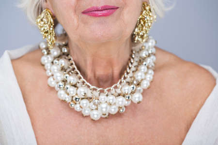 aristocracy: Senior, elegant woman with precious necklace and gold earrings