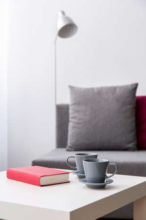 small table: Close up of book and two cups lying on small table, sofa and lamp in the background.