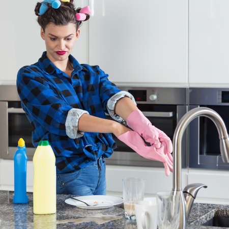 Disgusted young housewife taking off her rubber gloves