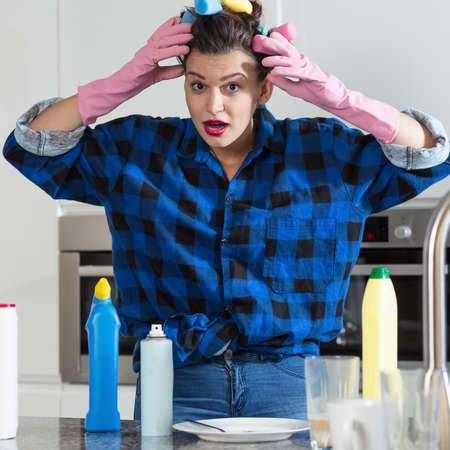 housekeeper: Young housekeeper exhausted of cleaning dirty dishes