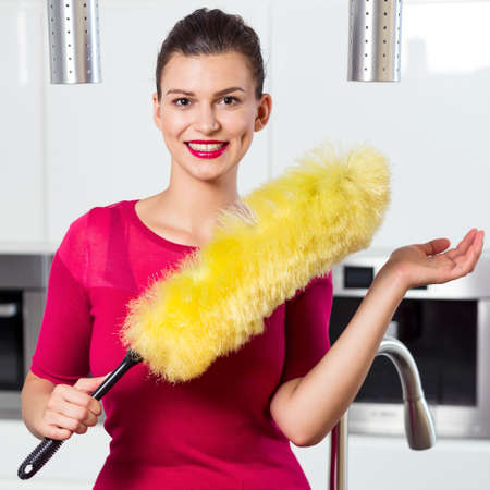 pedant: Smiling young woman with fluffy dust brush