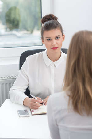 demanding: Image of woman during interview with demanding boss Stock Photo