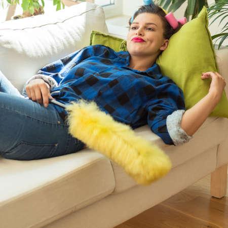 ama de casa: mujer joven perezoso que se reclina en el sofá durante la limpieza Foto de archivo