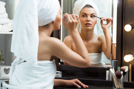 dressing table: Girl at dressing table in bathroom using mascara Stock Photo