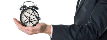 workaholic: Man in suit holding alarm clock in  his hand. Panorama, white background. Stock Photo
