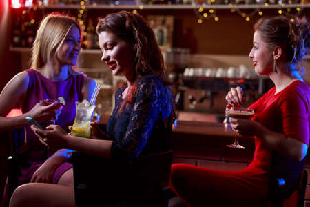 pretty dress: Friends relaxing in night club after long day Stock Photo