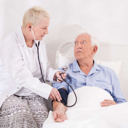 Medical examination of senior man lying in bed Stock Photo