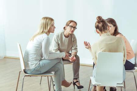 persona sentada: Las mujeres están sentados en el círculo durante la reunión
