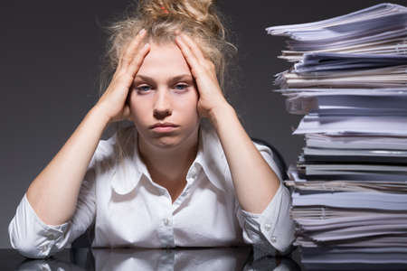 psychical: Young woman has lots of paperwork in the office
