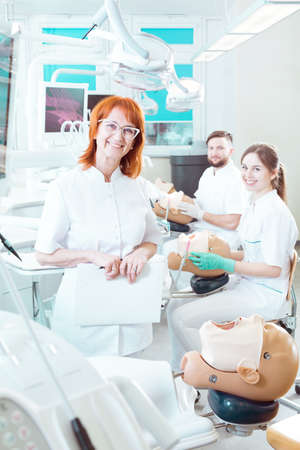 well equipped: Mature woman and two students of dentistry in well equipped classroom, dental manikin in the foreground