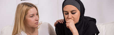 hijab: Blonde woman supporting her sad, muslim friend, light interior