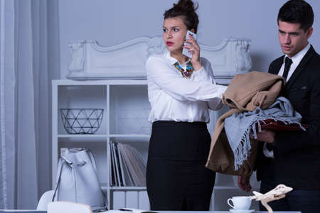 humiliated: Woman boss with cellphone and her humiliated assistant holding her things