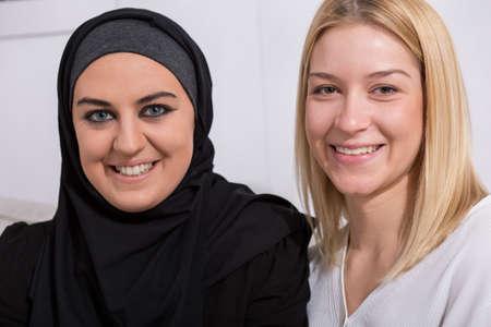 tolerancia: musulmán feliz en su hijab y europeo, amiga rubia Foto de archivo