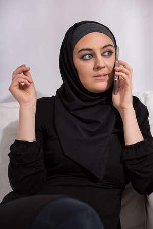 arab hijab: Muslim in black hijab talking on phone, sitting Stock Photo