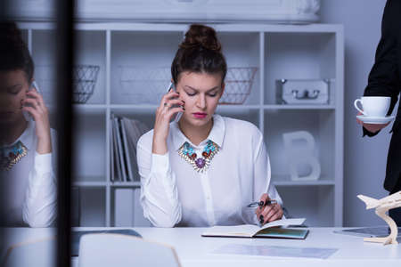 company job: Busy corporate woman sitting at desk with cellphone and notebook