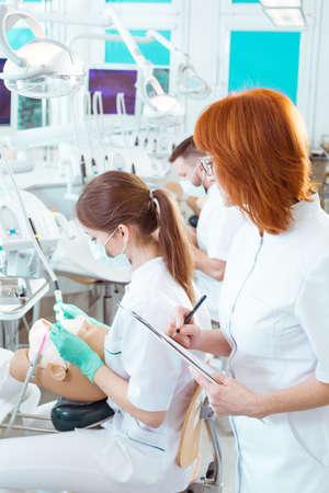 profesor alumno: Estudiante que trabaja en el maniquí dental y haciendo notas del profesor