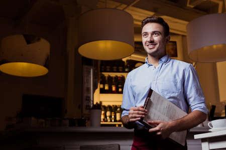 若いビジネスマンおよび彼の小さいレストランを笑顔