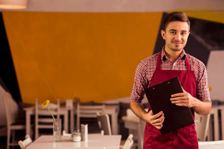 glad: Smiling young man glad of his job in restaurant