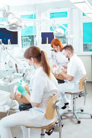 well equipped: Students of dentistry in well equipped class training on dental manikin Stock Photo