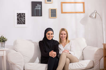 hijab: Happy muslim and european, blonde woman sitting together on sofa in light, cozy interior