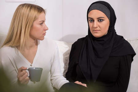 race relations: Blonde woman supporting sad muslim in hijab, sitting on sofa Stock Photo