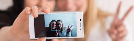 race relations: Muslim and her blonde friend taking selfie, panorama