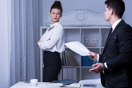 resignation: Man in suit giving his resignation to confident and attractive woman boss Stock Photo