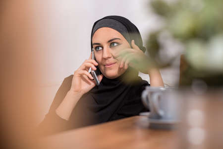 islam: Arab woman in black hijab talking on phone Stock Photo