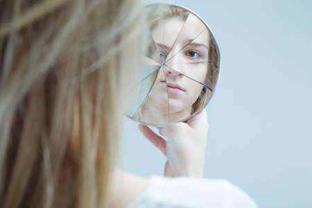 壊れたミラーを保持している精神的な障害を持つ女性の画像