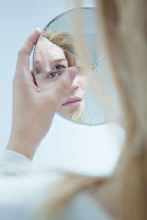 Afbeelding van vrouwelijke met een bipolaire stoornis Spiegel van de Holding Stockfoto