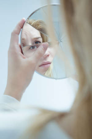 Image of female with bipolar disorder holding mirror