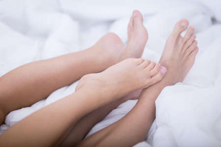 sex on bed: Close-up of feet of young couple in bed Stock Photo
