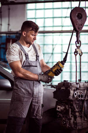 automotive technician: Image of automotive technician repairing broken engine