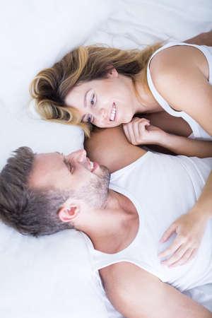 young couple sex: Счастливая молодая пара тратить утром в постели Фото со стока