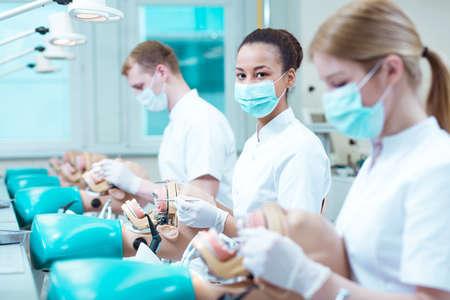 odontologa: estudiantes de odontología en máscaras médicas, dentales que trabajan en maniquíes Foto de archivo