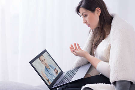 online: Ill woman in front of laptop talking online with doctor