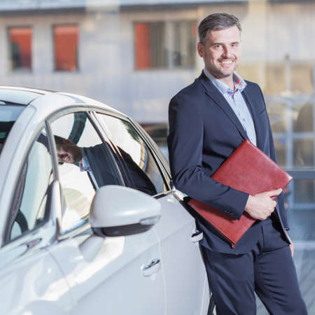 new automobile: Smiling businessman with new automobile Stock Photo