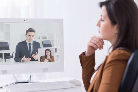 Young woman in front of computer during video conference with her boss
