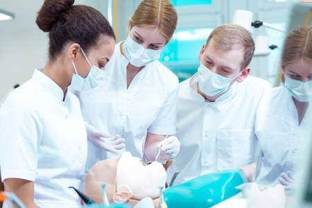 Dentistry students in medical masks training on manikin Banque d'images