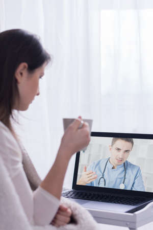 skype: Woman holding cup, sitting in front of laptop listening to skype doctor