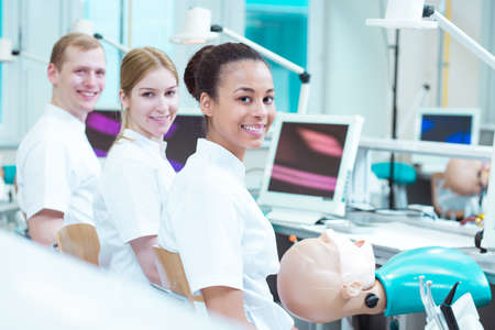 well equipped: Happy students of dentistry in well equipped, modern classroom