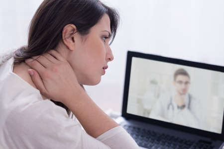 illness: doctor and woman with neck pain in front of laptop
