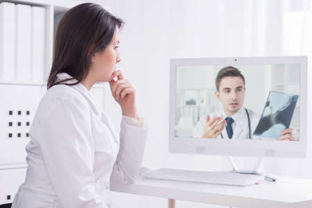 Doctor consulting medical problem with woman doctor via  internet Stock Photo