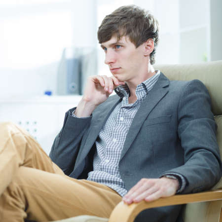 Young thoughtful businessman sitting in an armchair