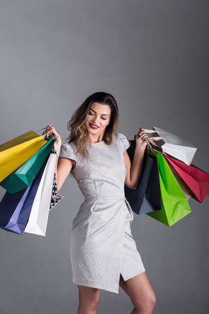 silver dress: Woman in silver dress holding many colorful shopping bags, smiling