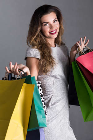silver dress: Smiling woman in silver dress holding many, colorful paper bags